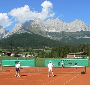 Red-clay tennis courts and Wilder Keiser Mountains in Stanglwirt, Austria